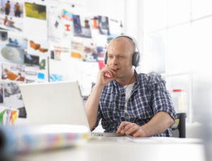 man listening to headphones at work